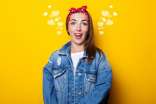 Jovem simpática em uma faixa de cabelo, com uma jaqueta jeans em uma parede amarela.