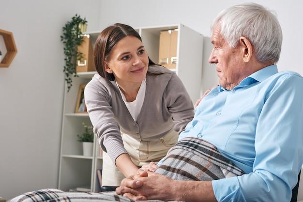 Jovem simpática especialista em cuidados de enfermagem perguntando a um homem sênior sobre suas necessidades enquanto cuida dele