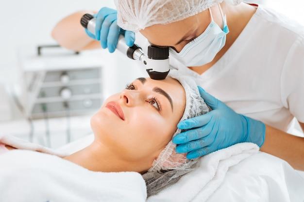 Jovem simpática examinando a pele durante uma visita a uma clínica dermatológica