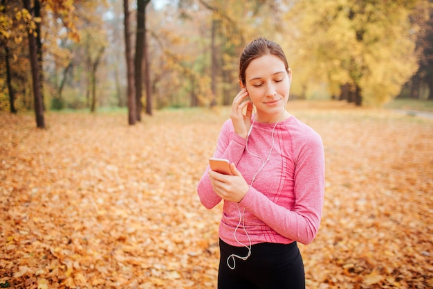 Jovem simpática fica sozinha no parque e mantém os olhos fechados. ela ouve música através de fones de ouvido. modelo mantém o telefone nas mãos. ela gosta de tempo. mulher está sozinha.