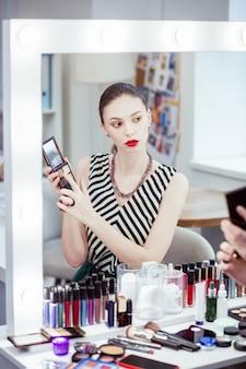 Jovem simpática olhando no espelho enquanto escolhe a cor da sombra