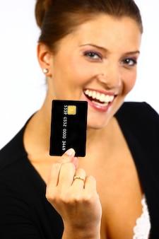 Jovem simpática segurando um cartão de crédito preto