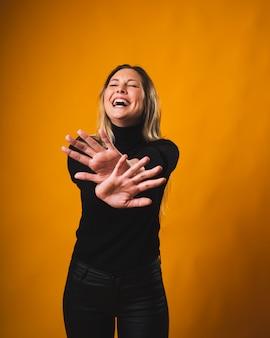 Jovem simpática sorrindo e coloca as mãos como se não quisesse tirar uma foto, vestindo uma camisa preta e calça