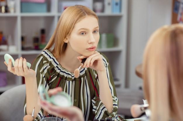 Jovem simpática tocando seu queixo enquanto olha seu reflexo no espelho