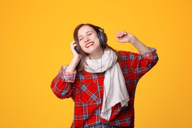 Jovem simpática usando cachecol e camisa xadrez ouvindo música nos fones de ouvido