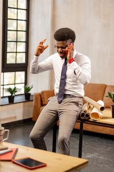 Jovem simpático falando ao telefone enquanto conversava sobre trabalho