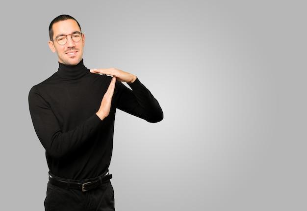 Jovem simpático fazendo um gesto de pausa com as mãos