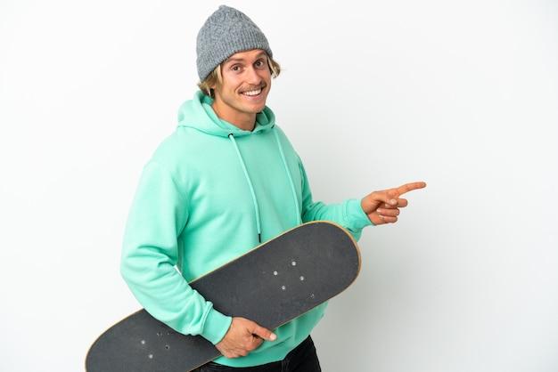 Jovem skatista loira isolada no fundo branco apontando o dedo para o lado