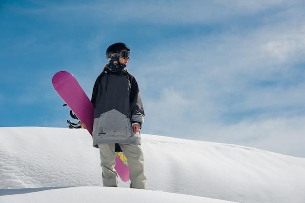 Jovem snowboarder feminino em pé na encosta da montanha