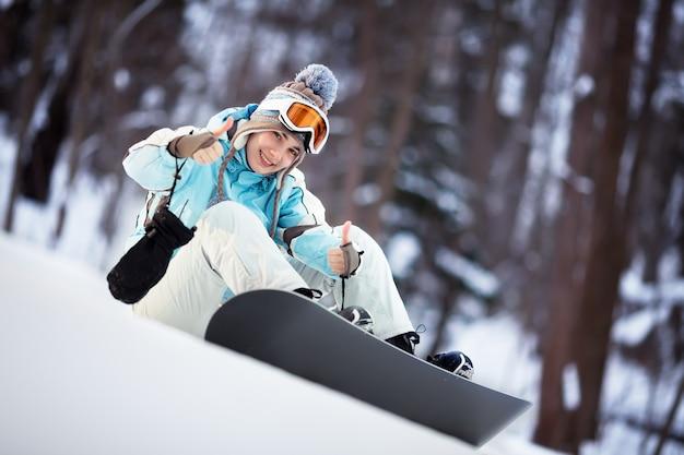 Jovem snowboarder sentada numa encosta com os polegares para cima