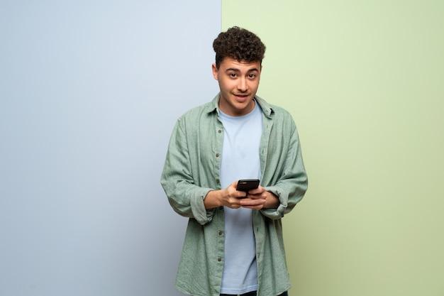 Jovem, sobre fundo azul e verde, enviando uma mensagem com o celular