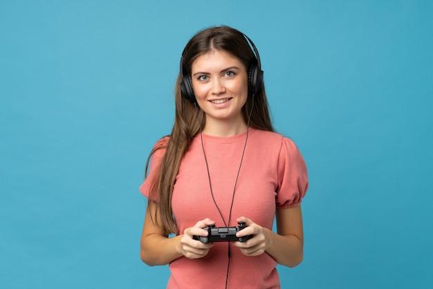 Jovem sobre fundo azul isolado, jogando em videogames