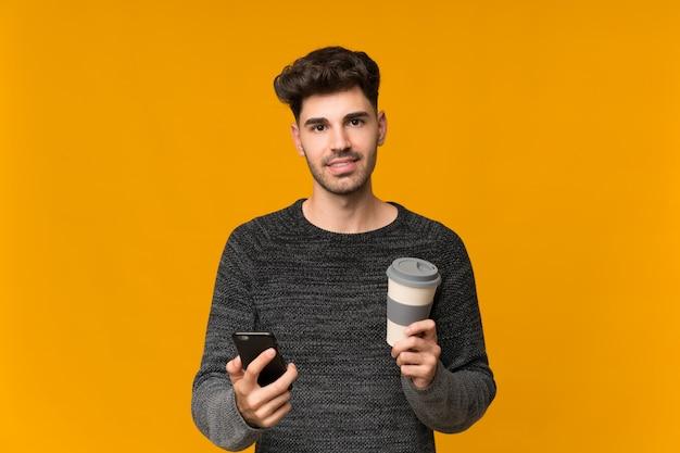 Jovem sobre isolado segurando café para levar e um celular