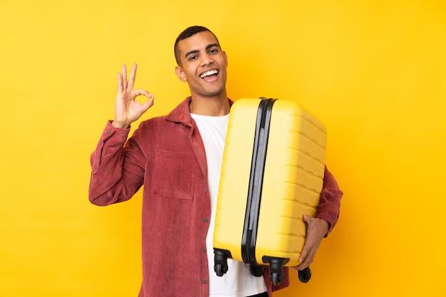Jovem sobre parede amarela isolada em férias com mala de viagem e fazendo sinal de ok