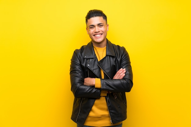 Jovem sobre parede amarela isolada, mantendo os braços cruzados na posição frontal