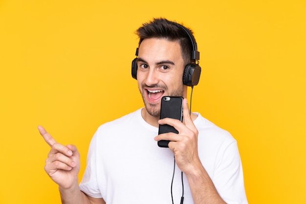 Jovem sobre parede amarela, ouvindo música com um celular e cantando