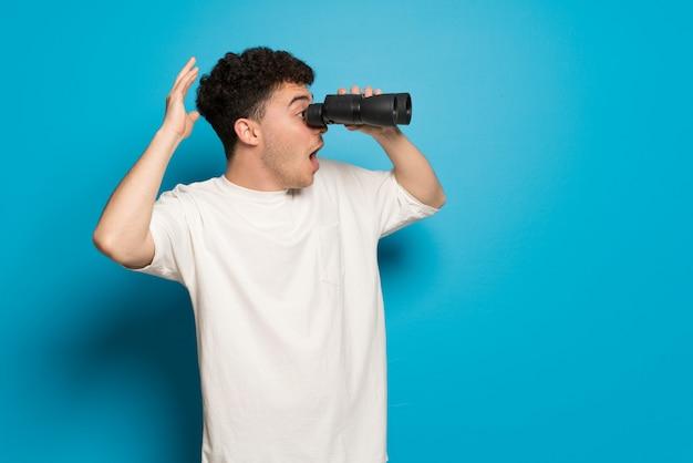 Jovem sobre parede azul e olhando à distância com binóculos