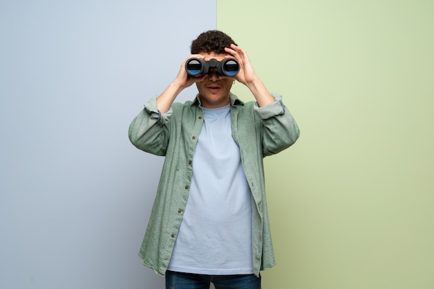 Jovem sobre parede azul e verde e olhando à distância com binóculos