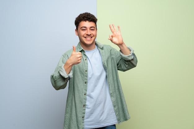 Jovem sobre parede azul e verde, mostrando sinal de ok e dando um polegar para cima gesto