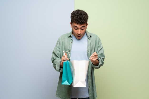 Jovem sobre parede azul e verde surpreendeu enquanto segura um monte de sacolas