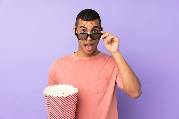 Jovem sobre parede azul isolada surpreendido com óculos 3d e segurando um grande balde de pipocas