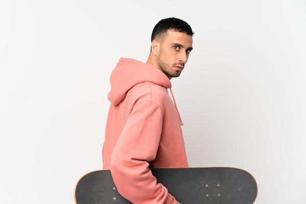 Jovem sobre parede branca isolada com skate em posição traseira