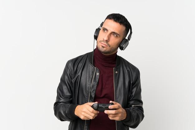 Jovem sobre parede branca isolada, jogando em videogames