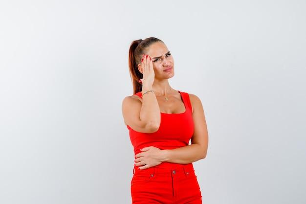 Jovem sofre de dor de cabeça em camiseta vermelha, calças vermelhas e parece dolorosa, vista frontal.