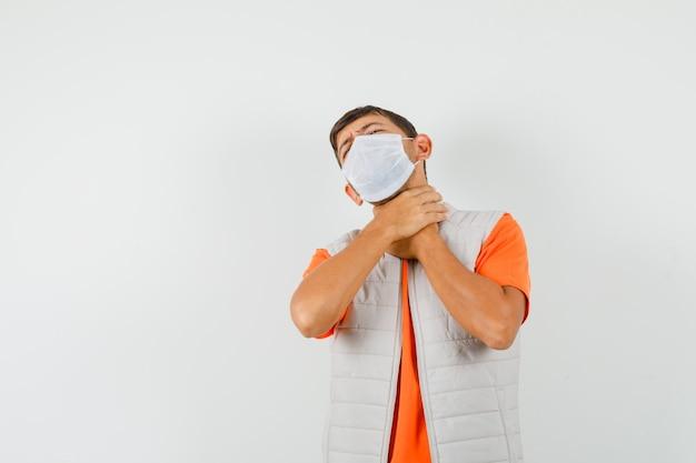 Jovem sofre de dor de garganta na camiseta, jaqueta, máscara e parece doente.