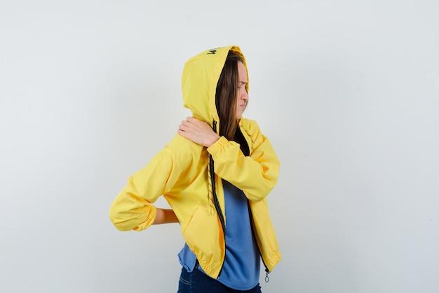 Jovem sofre de dor nas costas em t-shirt, jaqueta e parecendo cansada, vista frontal.