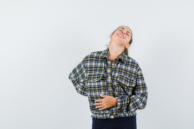 Jovem sofre de dor nas costas em uma camisa, shorts e parecendo cansada, vista frontal.