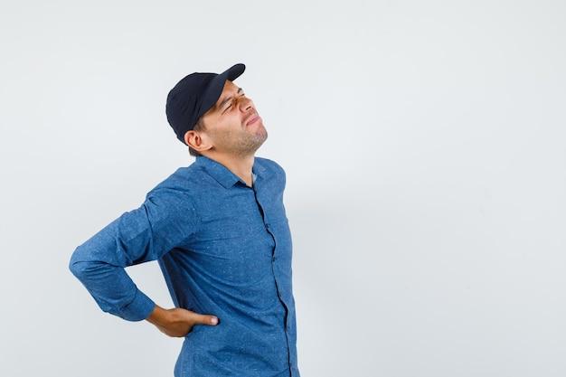 Jovem sofre de dor nas costas, vestindo uma camisa azul, boné e parecendo dolorido. vista frontal.