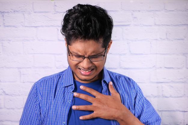 Jovem sofre de dor no coração e segurando o peito com a mão.