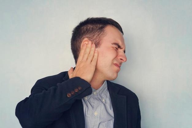 Jovem sofre de dor no ouvido direito, sobre fundo azul. conceito médico. doenças do ouvido. inflamação no ouvido.