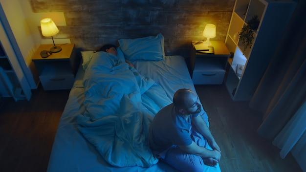 Jovem sofre de insônia enquanto sua esposa está dormindo. luz da lua.
