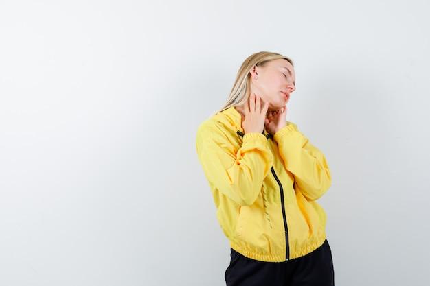 Jovem sofre de pescoço em jaqueta amarela, calça e parecendo cansada, vista frontal.
