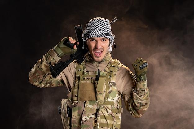 Jovem soldado camuflado com metralhadora em um tanque de guerra do exército da palestina de superfície escura