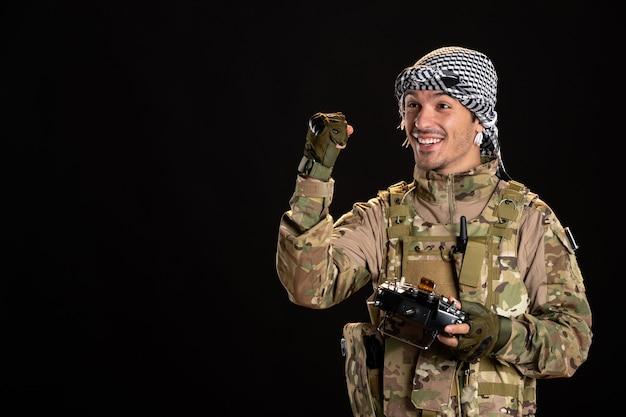 Jovem soldado camuflado usando o controle remoto na parede preta