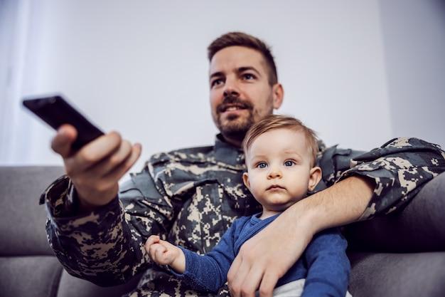 Jovem soldado corajoso barbudo passando bons momentos com seu filho amado. eles estão assistindo televisão. homem com controle remoto nas mãos.