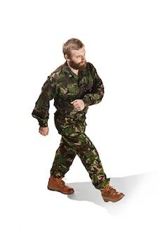 Jovem soldado do exército vestindo uniforme de camuflagem vai isolado no estúdio branco
