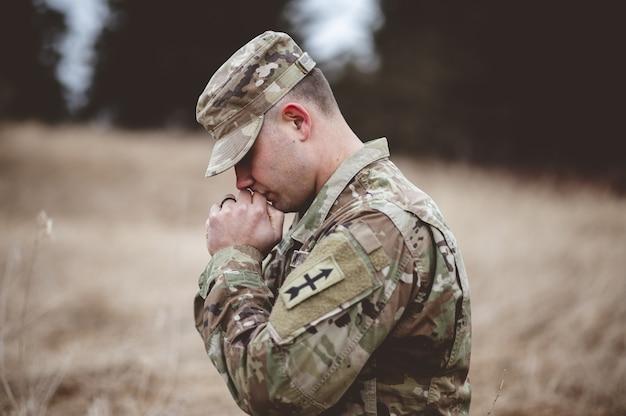 Jovem soldado orando em um campo