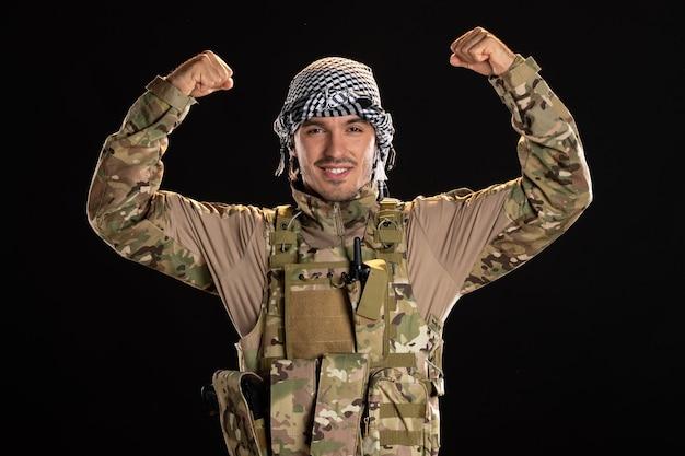 Jovem soldado sorridente camuflado flexionando-se na parede preta