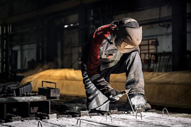 Jovem soldador de uniforme, máscara de soldagem e soldadores de couro solda de metal