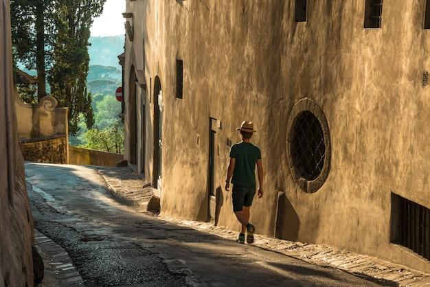 Jovem solitário caminhando na rua ao lado de um antigo prédio de concreto