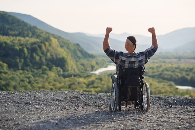 Jovem solitário em uma cadeira de rodas, aproveitando o ar fresco em um dia ensolarado na montanha