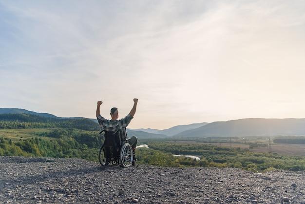 Jovem solitário em uma cadeira de rodas levantou as mãos alegrando-se com sua vitória na montanha