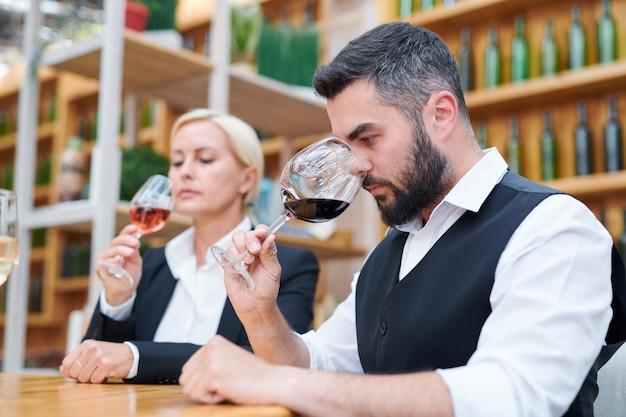 Jovem sommelier barbudo em trajes formais cheirando um novo tipo de vinho tinto em uma taça de vinho enquanto examina sua qualidade