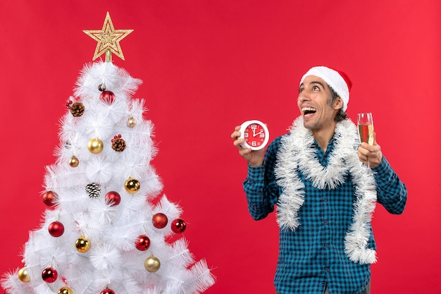 Jovem sonhador com chapéu de papai noel e segurando uma taça de vinho e um relógio em pé perto da árvore de natal no vermelho