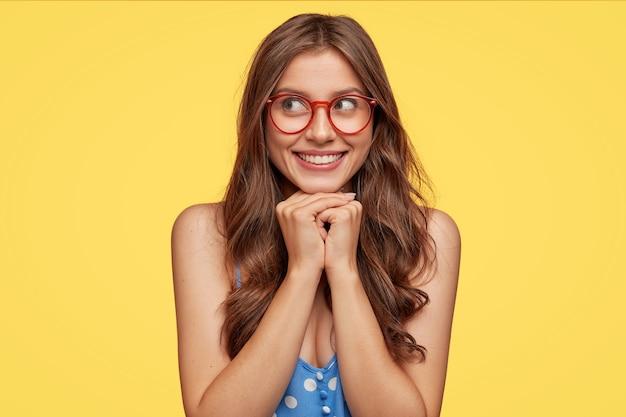 Jovem sonhadora de óculos posando contra a parede amarela