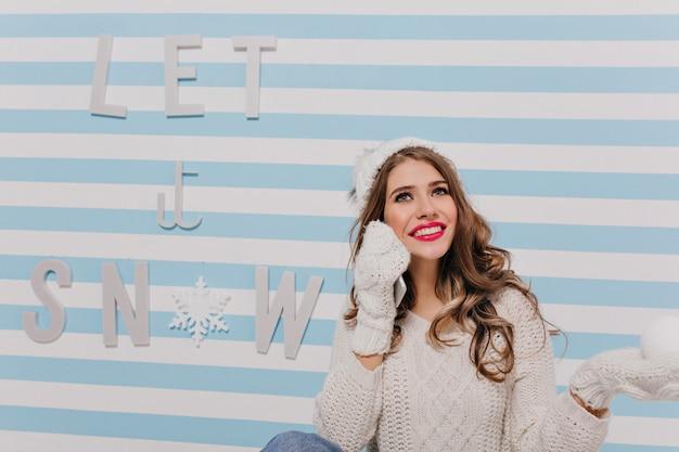 Jovem sonhadora de olhos azuis e humor de ano novo posando sentada no chão